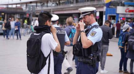 德國警察讓蒙面人摘掉面罩